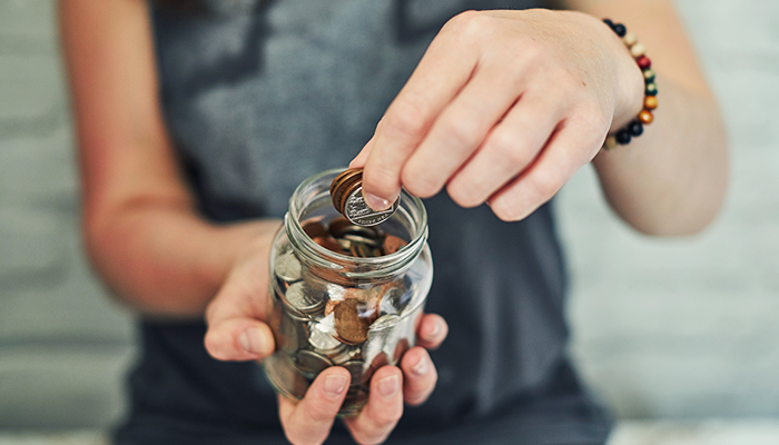 Woman taking coins from a jar